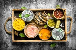 Various canned products in tin cans on a wooden tray. On a rustic background. Credit: SarapulSar38.