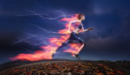 Side view of sporty woman running fast against stormy sky with lightning and tongues of flame.