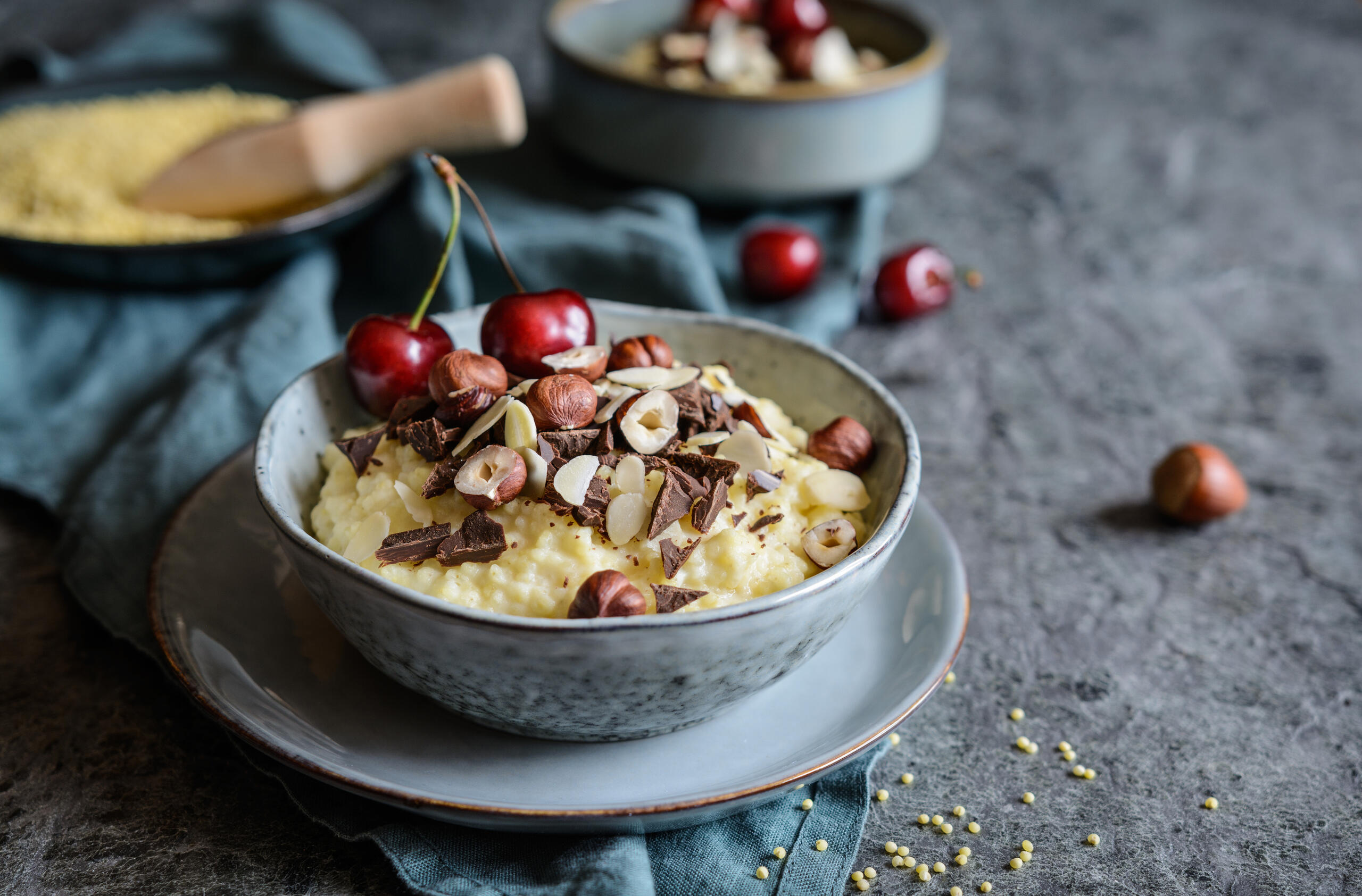 Nutritious millet porridge topped with chocolate pieces, hazelnuts, almond slices and cherry. Credit: NoirChocolate.
