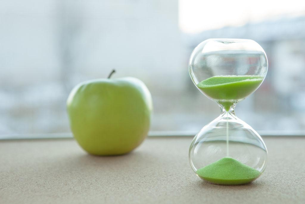 Hourglass with an apple in the background