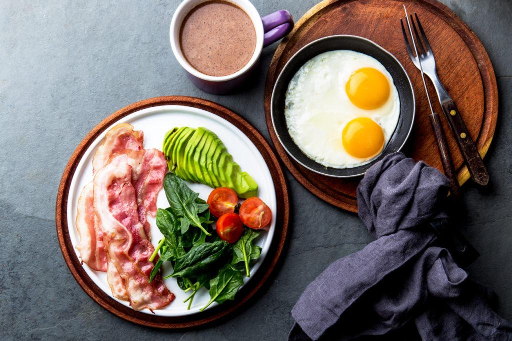 One ketogenic diet breakfast: Fried egg, bacon and avocado, spinach and bulletproof coffee.
