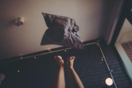 Photo of a cheerful young woman, still playful at bedtime, trowing pillow in the air.