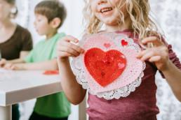 Child holding Valentine's day card up to her heart.