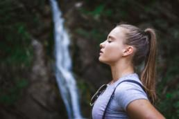 Woman breathing fresh air in front of a waterfall.