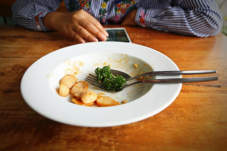 Image: Person finished meal and play smartphone.
