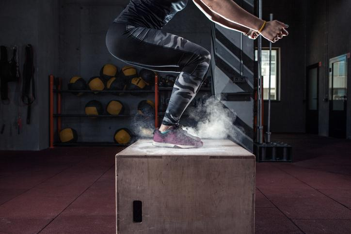 Young woman jumping box and talc powder departs from under feet.