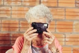 Older woman holding up a camera. Photo by Tiago Muraro on Unsplash.