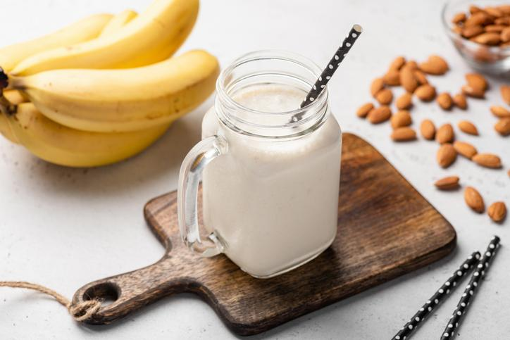 Banana protein smoothie in drinking glass on wooden serving board.