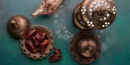 Bronze plate with dates, coffee cup, lantern and lamp on dark green wooden background. Ramadan kareem.