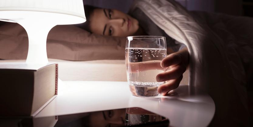 Woman drinking water in bed. Drink water as soon as you wake up daily for Ramadan!