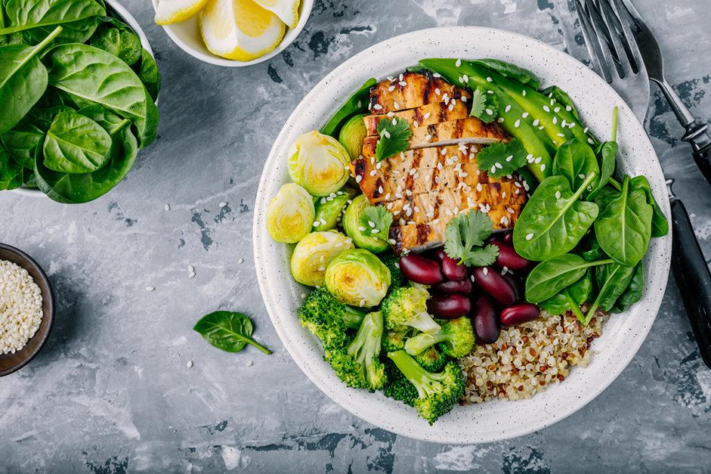 Healthy buddha bowl lunch with grilled chicken, quinoa, spinach, avocado, brussels sprouts, broccoli, red beans with sesame seeds.