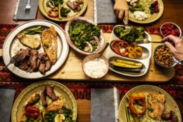 A ketogenic meal laid out on a dining table with the hands of people serving themselves. A keto diet is a low carb, high fat diet.