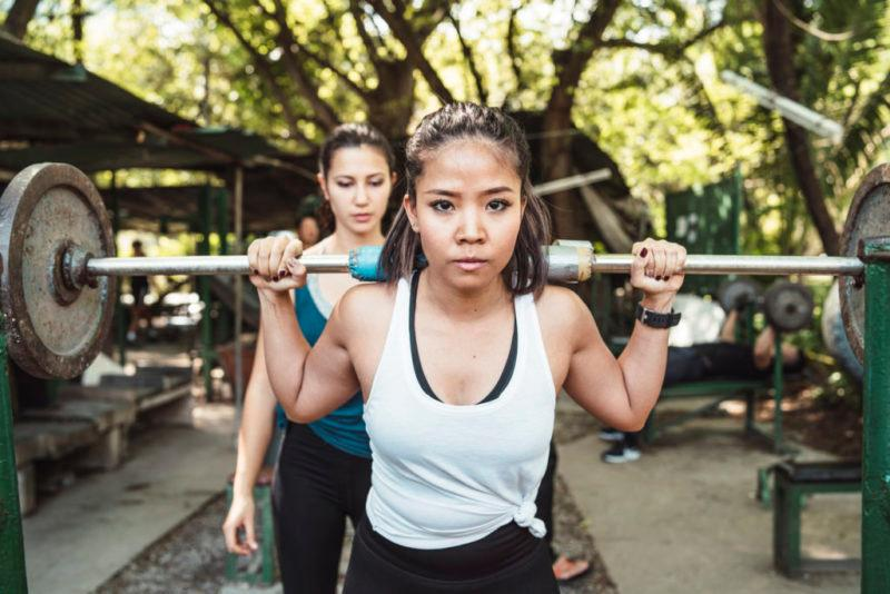 Two young adult women weight lifting outdoor with a barbell. When is the last time you pumped some iron? Don't be afraid - just start.