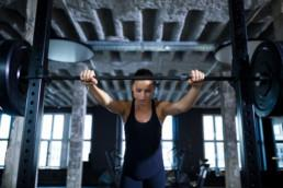 Female athlete gripping barbell in gym.