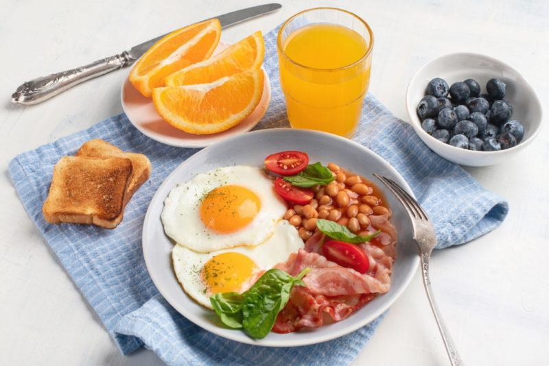 Plate of breakfast with fried eggs, bacon, beans, orange juice and toasts.