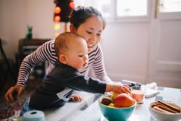 Brightly lit image of a young Thai mom with her little baby boy. They're spending time together at home, playing with toys and having some snacks.