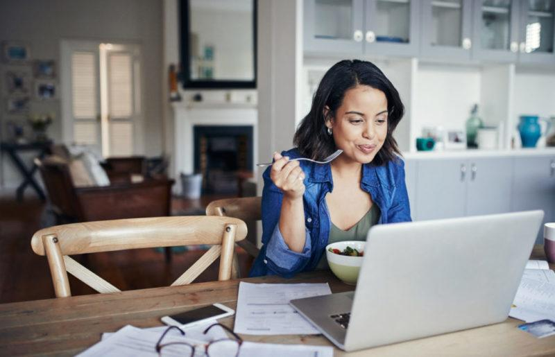 Shot of a young woman using a laptop and having a salad while working from home.