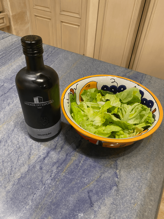 a bottle of olive oil next to a bowl of mixed greens sitting on a table.