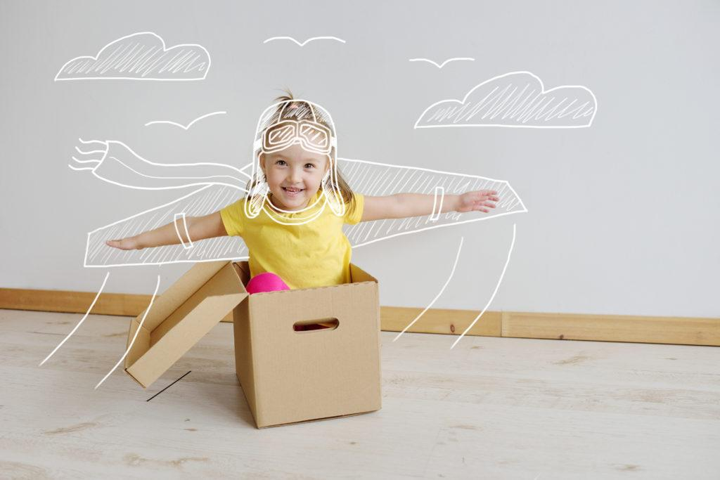 Cute little girl playing with cardboard airplane on a white background.