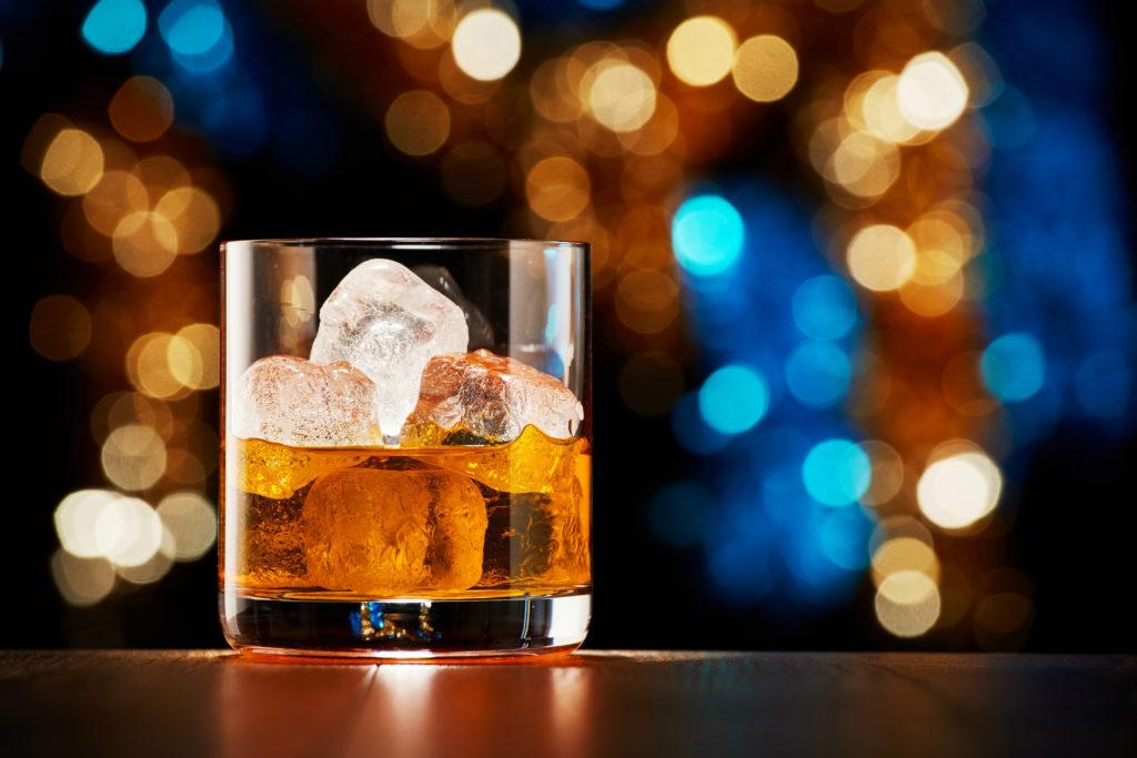 Glass of whiskey with ice on colorful Christmas lights bokeh background