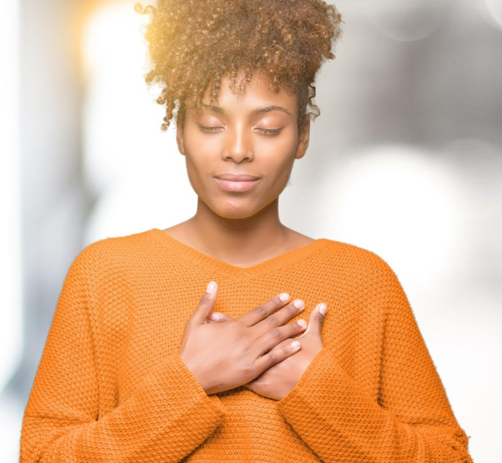 Beautiful young african american woman over isolated background smiling with hands on chest with closed eyes and grateful gesture on face. Health concept.