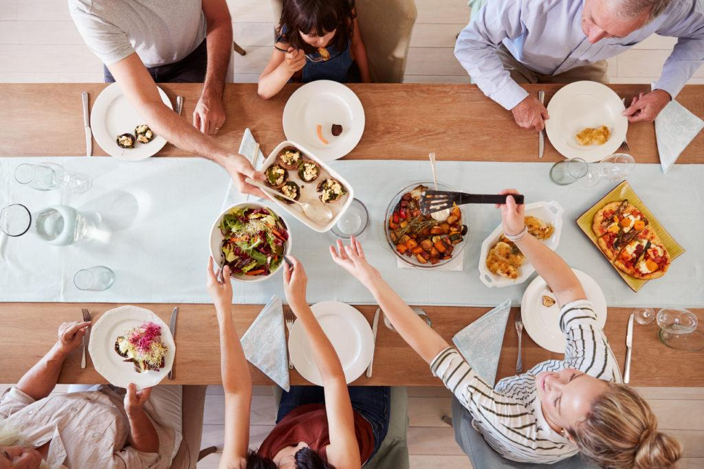 Family sitting at a dinner table together serving a meal, overhead view