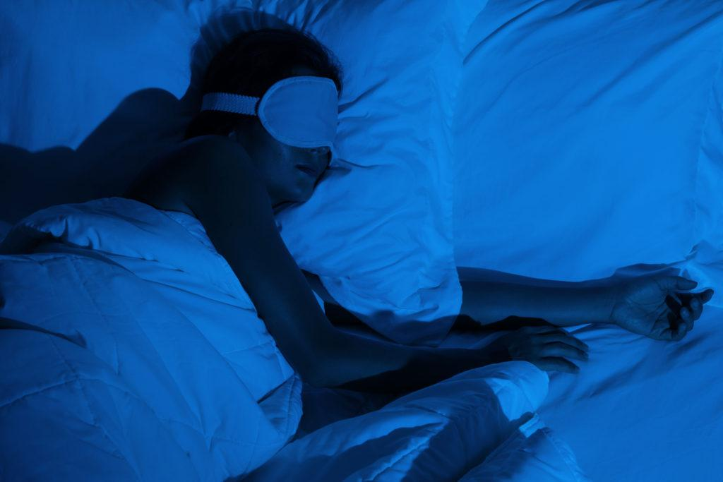Woman sleeping with a sleep mask on her eyes in the bedroom