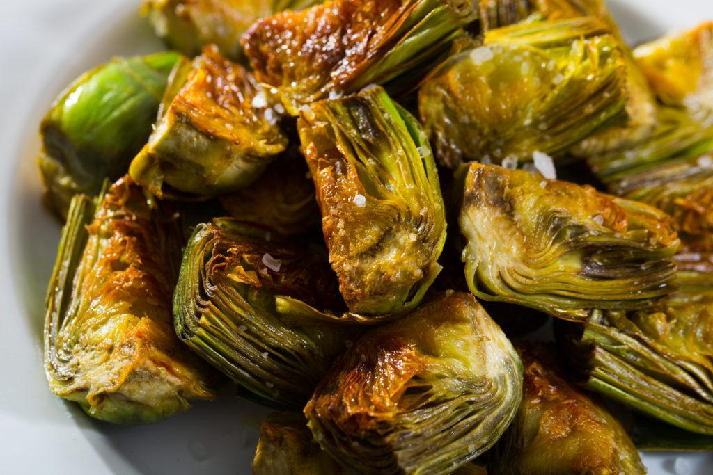Chopped artichokes fried in oil served on white plate.