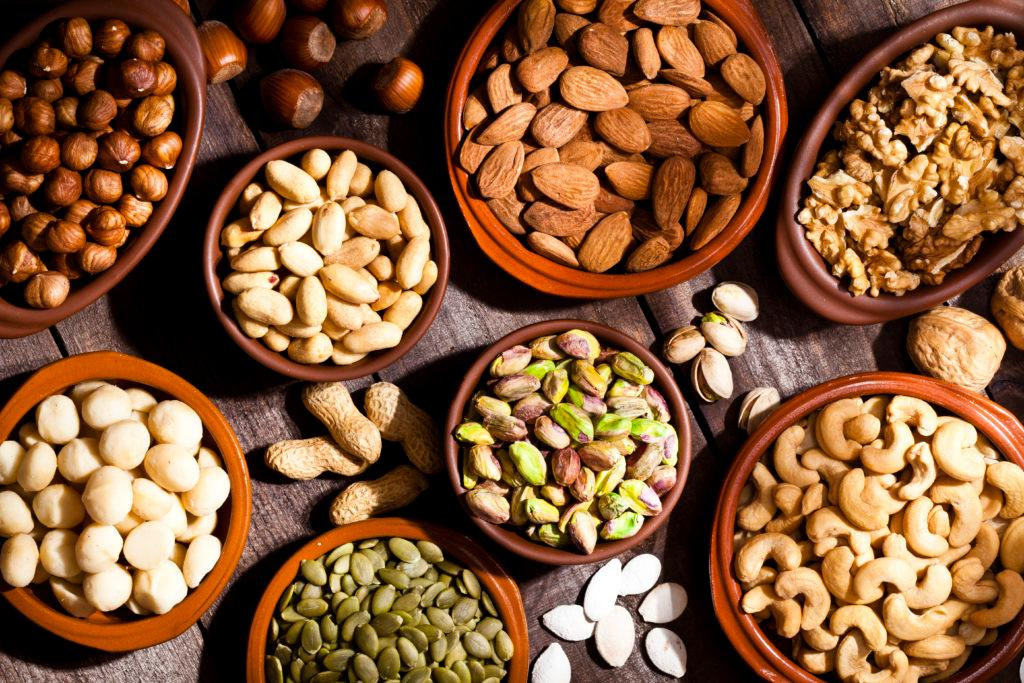 Top view of a rustic wood table filled with a large assortment of nuts like pistachios, hazelnut, pine nut, almonds, pumpkin seeds, peanuts, cashew and walnuts. Some nuts are in brown bowls and others are placed directly on the table. Predominant color is brown. DSRL studio photo taken with Canon EOS 5D Mk II and Canon EF 100mm f/2.8L Macro IS USM