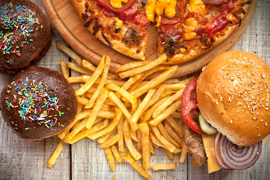 ,Closeup of home made burgers , french fries and donuts on wooden background