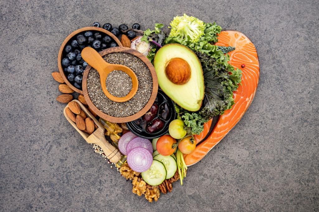 Ingredients for healthy foods selection on dark stone background. Balanced healthy ingredients of unsaturated fats for the heart and blood vessels.