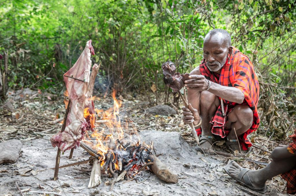 Arusha, Tanzania, 7Th September 2019: Maasai man cooking meat on fire