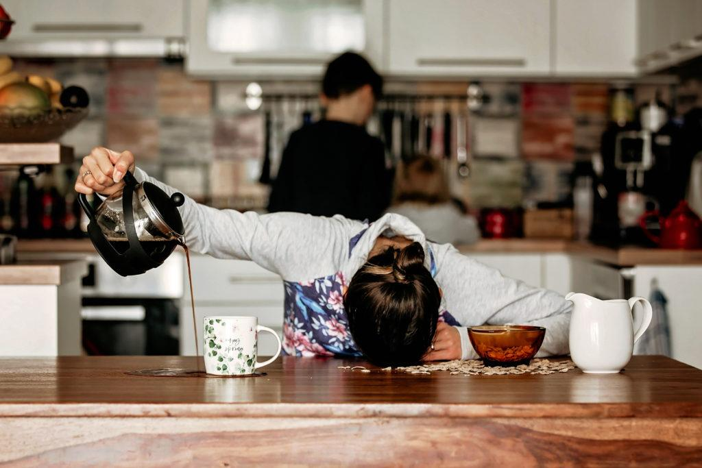 Woman lying on kitchen table after sleepless night, trying to drink coffee