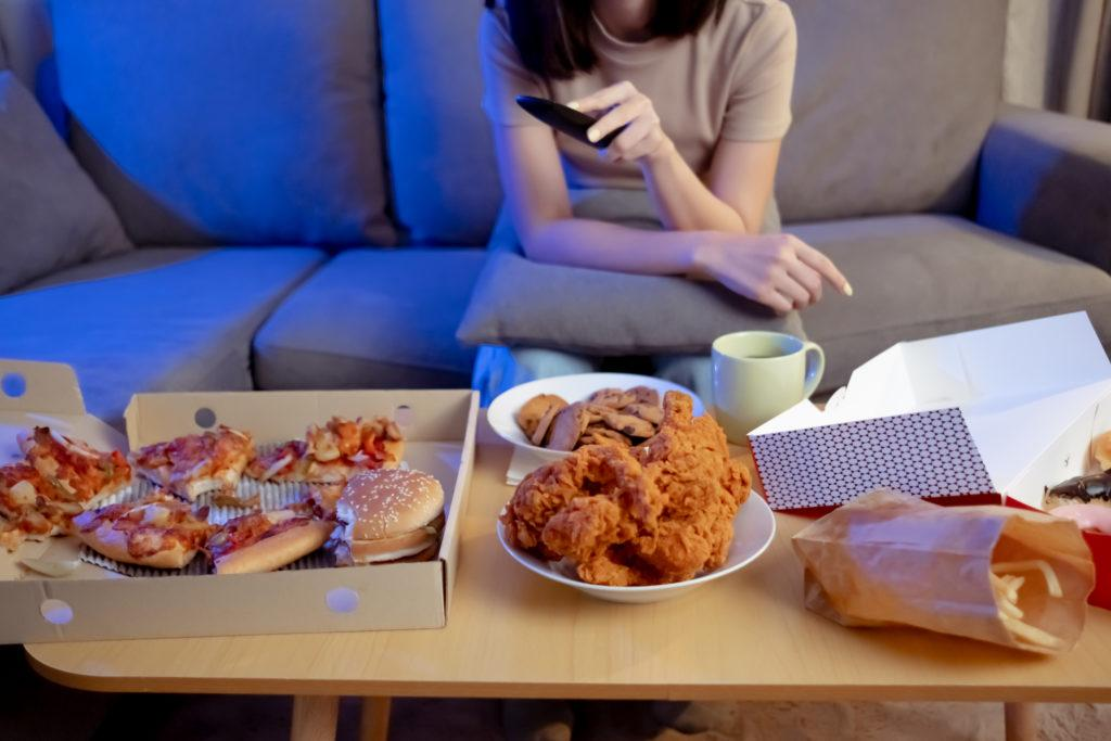 Young asian woman takeaway eating junk food unhealthy on couch watching tv series eatery fast food and drinking in living room enjoy happiness at home.