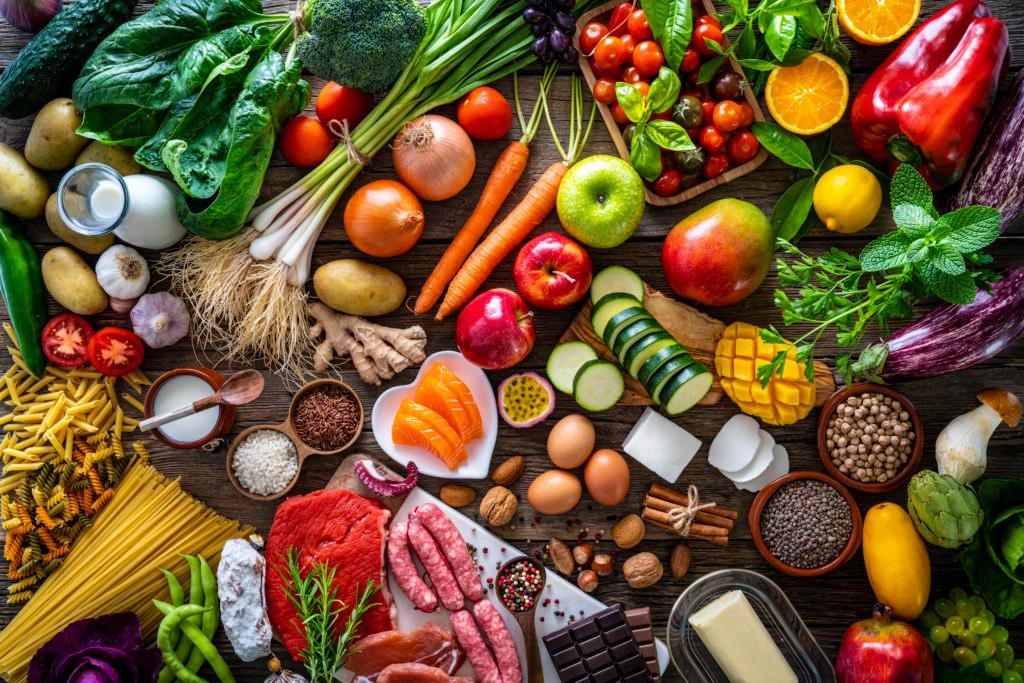 Food and drink large arrangement with carbohydrates protein vegetables and fruits legumes and dairy products on rustic board table.