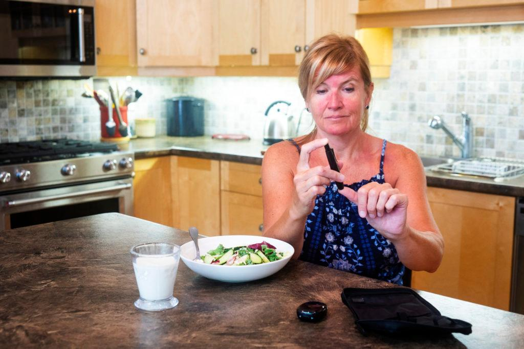 A middle age female diabetic patient testing her blood sugar at home prior to eating a healthy meal.