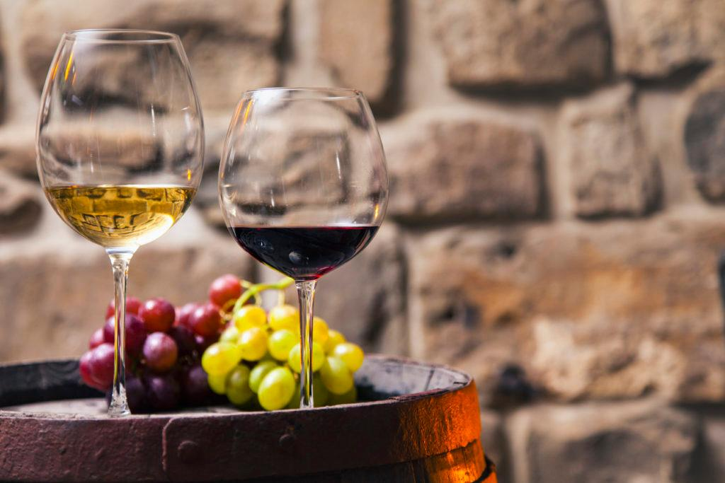 Two glasses of red and white wine on barrel in the cellar