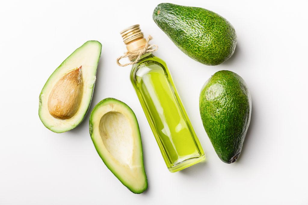 Glass bottle natural avocado oil, three fresh avocados on a white table. Top view