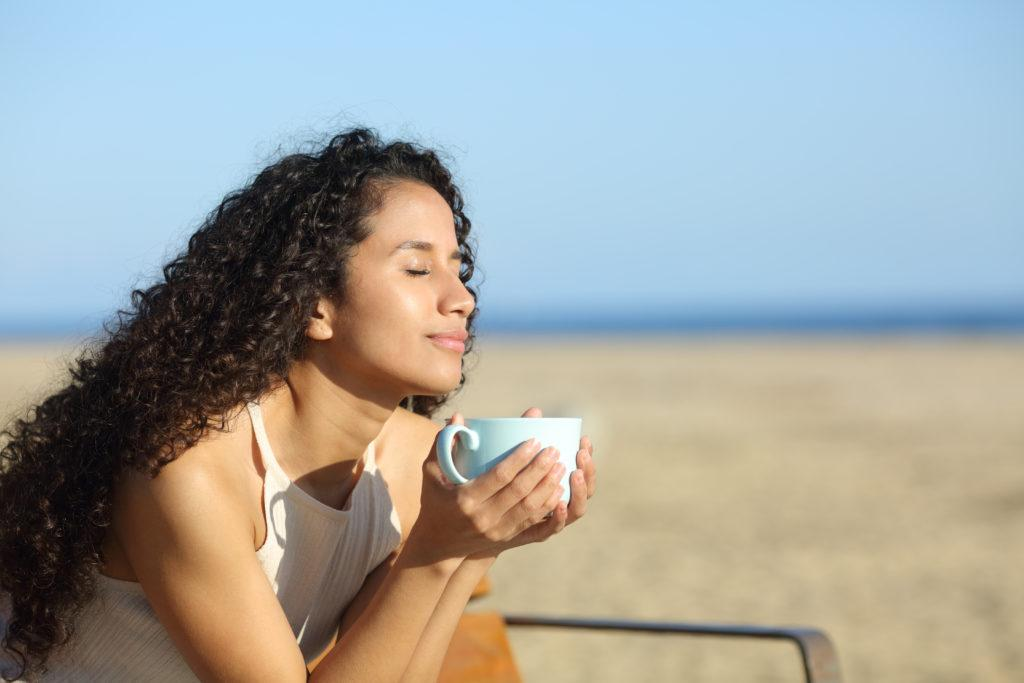 Latin woman enjoying a cup of coffee breathing fresh air on the beach a sunny day