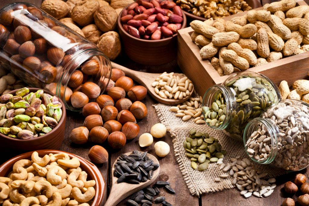 Horizontal shot of a rustic wood table filled with a large assortment of nuts like pistachios, hazelnut, pine nut, almonds, pumpkin seeds, sunflower seeds, peanuts, cashew and walnuts. Some nuts are in brown bowls and others in glass jars. Predominant color is brown.