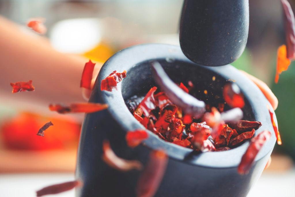 Action image of dried chilli peppers being crushed in a mortar and pestle. The chillis are flying out of the bowl as they are being smashed. Chillis are mostly whole.